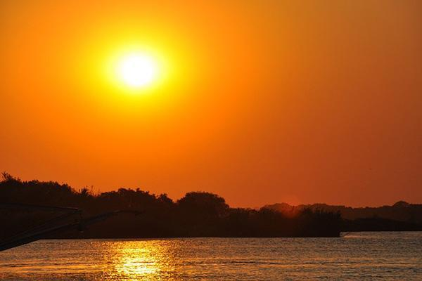 The setting sun paints the sky over the Zambezi River a fiery orange in Zimbabwe
